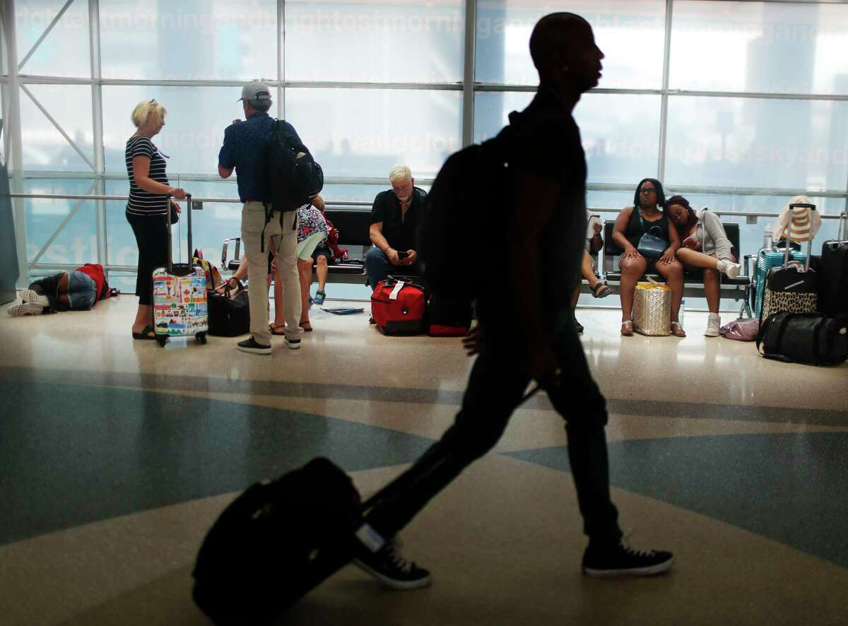 FILE- In this June 29, 2018, file photo, travelers gather on benches to wait for delayed and arriving flights as others make their way to to their gate at the Fort Lauderdale?-Hollywood International Airport in Fort Lauderdale, Fla. As summer vacationers start to pack up and head home, Congress is considering a sweeping tally of proposals that could affect travelers, from dictating seat size and legroom to rolling back rules that require airlines to advertise the full price of a ticket. (AP Photo/Brynn Anderson, File)