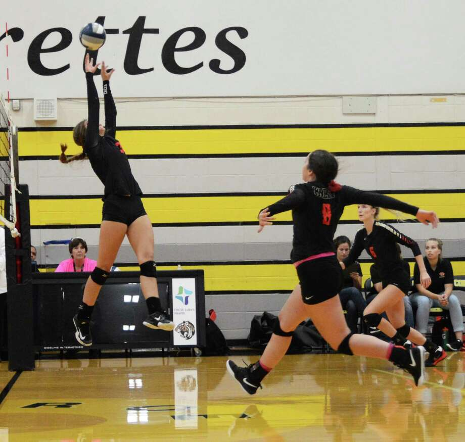 Caney Creek's Blakely Niles tries to set up outside hitters Madison Roe (8) and Kya Eubanks (6) against Conroe on Tuesday, August 7, 2018, at Conroe High School. Photo: Keith MacPherson / Keith MacPherson