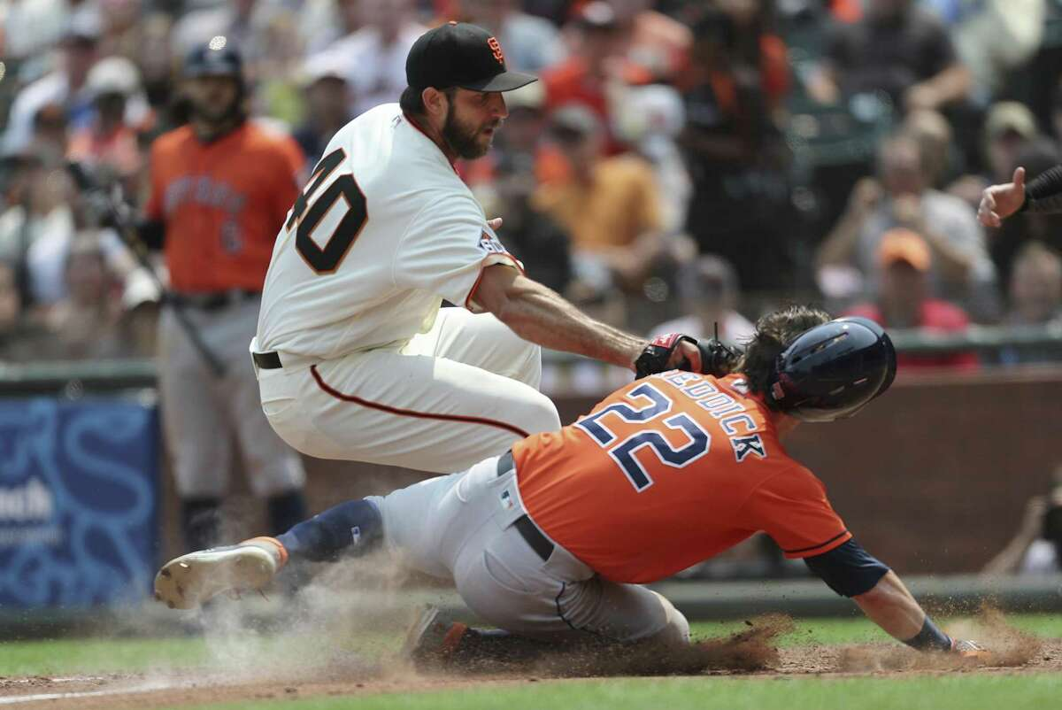A bid by the Astros' Josh Reddick to score in the sixth comes up empty as Giants pitcher Madison Bumgarner tags him out after a pitch got away from catcher Nick Hundley.