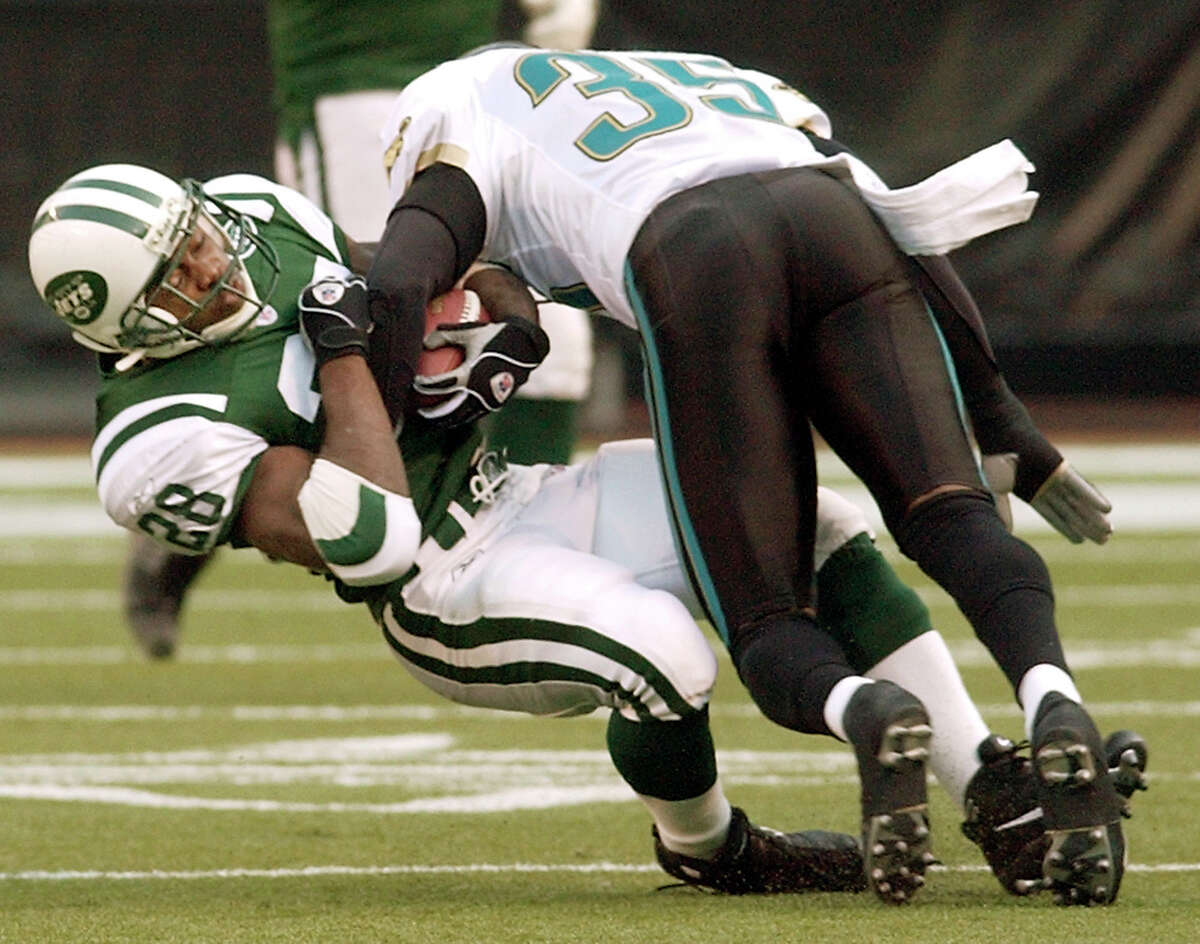 FILE - In this Nov. 23, 2003, file photo, Jacksonville Jaguars safety Deke Cooper brings down New York Jets running back Curtis Martin during the first quarter of an NFL football game at Giants Stadium in East Rutherford, N.J. Martin wishes the NFL?'s new rule that players can?'t lead with their helmets existed when he was on the field because he thinks it?'ll extend careers and hopes the current generation understands why it?'s in place. (AP Photo/Kathy Willens, File)