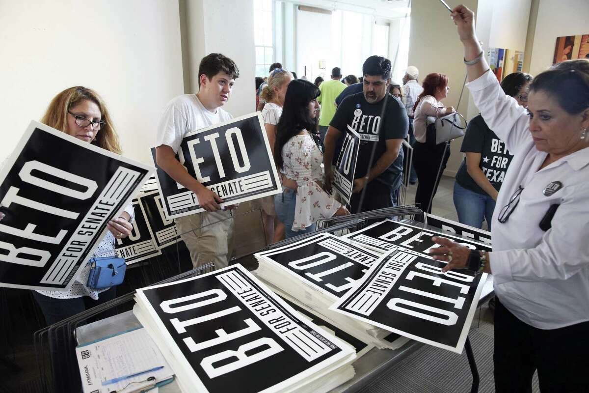 Volunteers in San Antonio distribute signs for Demo- cratic Senate candidate Beto O'Rourke. Elsewhere in Texas, women who back Democrats meet behind closed doors.