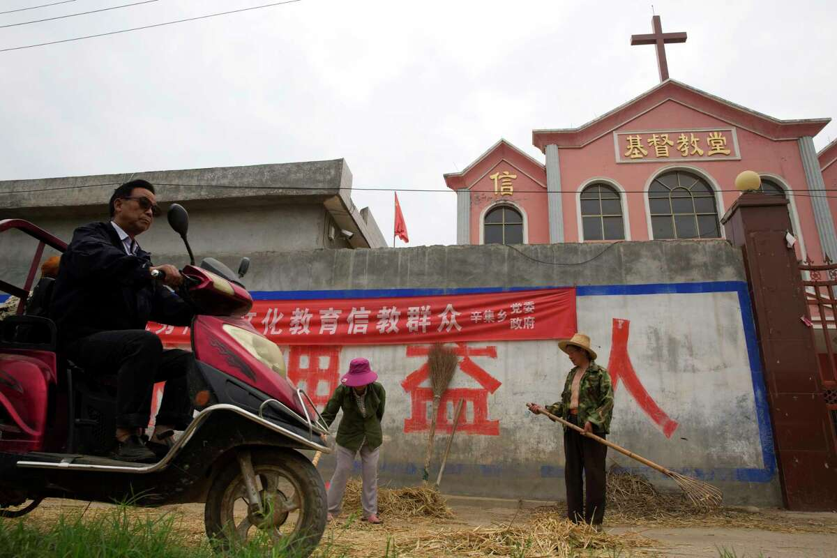 """In this photo taken Saturday, June 2, 2018, a man rides past workers tossing hay outside a church with part of a slogan that reads """"Educate the believers with excellent Chinese traditional culture"""" near the city of Pingdingshan in central China's Henan province. Under President Xi Jinping, China's most powerful leader since Mao Zedong, believers are seeing their freedoms shrink dramatically even as the country undergoes a religious revival. Experts and activists say that as he consolidates his power, Xi is waging the most severe systematic suppression of Christianity in the country since religious freedom was written into the Chinese constitution in 1982. (AP Photo/Ng Han Guan)"""