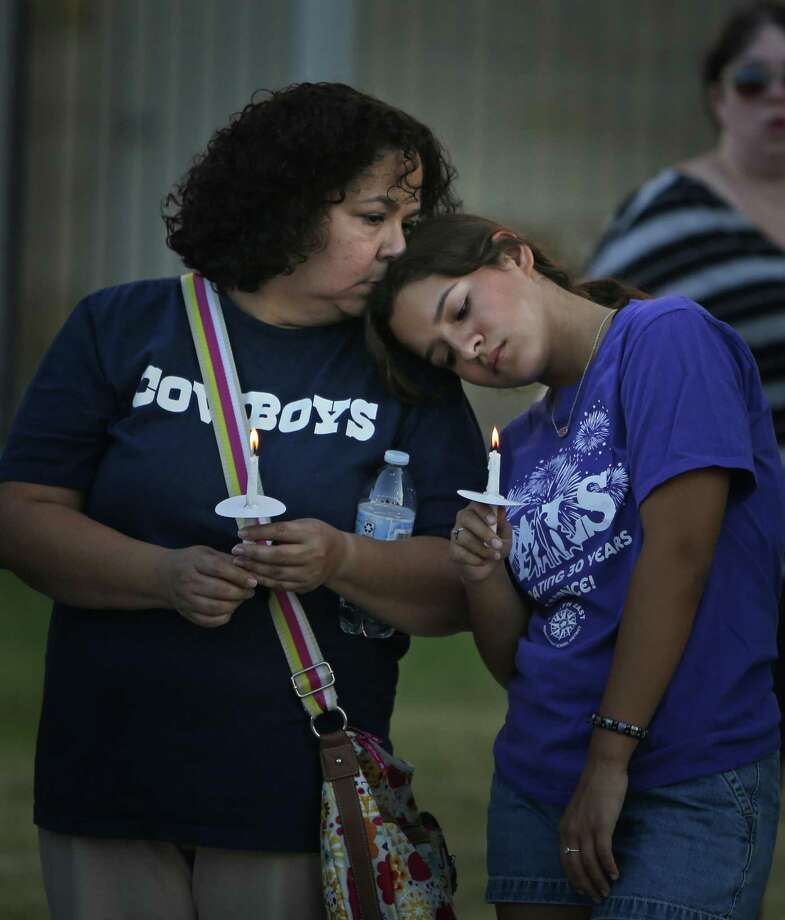 """Melanie Baltazar is comforted by mom Naomi as they join friends at a vigil for Emmanuel """"Manny"""" Pena on Tuesday evening at Roosevelt High School. Photo: Ronald Cortes /Contributor / 2018 Ronald Cortes"""