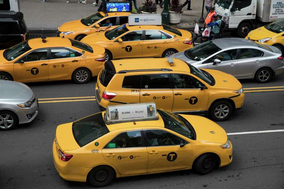 In this Wednesday, Aug. 1, 2018 photo, yellow cabs make their way across 42nd Street outside Grand Central Terminal in New York. New York City taxi regulators have approved new pay standards for app-based car services that they say will raise drivers' annual earnings by $10,000 a year, making it the first U.S. city to set such minimum pay standards. Photo: Mary Altaffer / Copyright 2018 The Associated Press. All rights reserved.