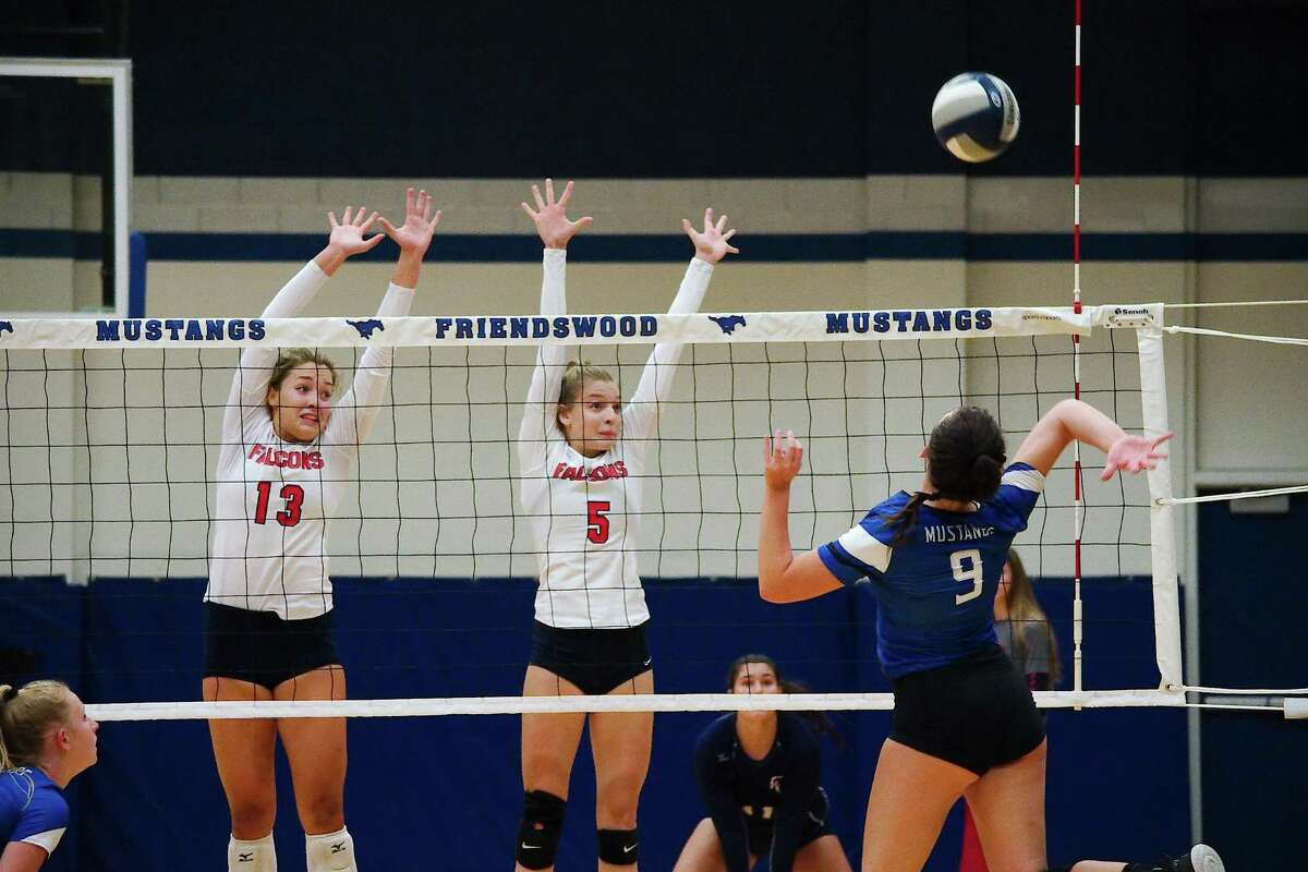 Clear Lake's Libby Saunders (13) and Clare Mills (5) go high to block a shot by Friendswood's Lauren Hubbard (9) Tuesday.