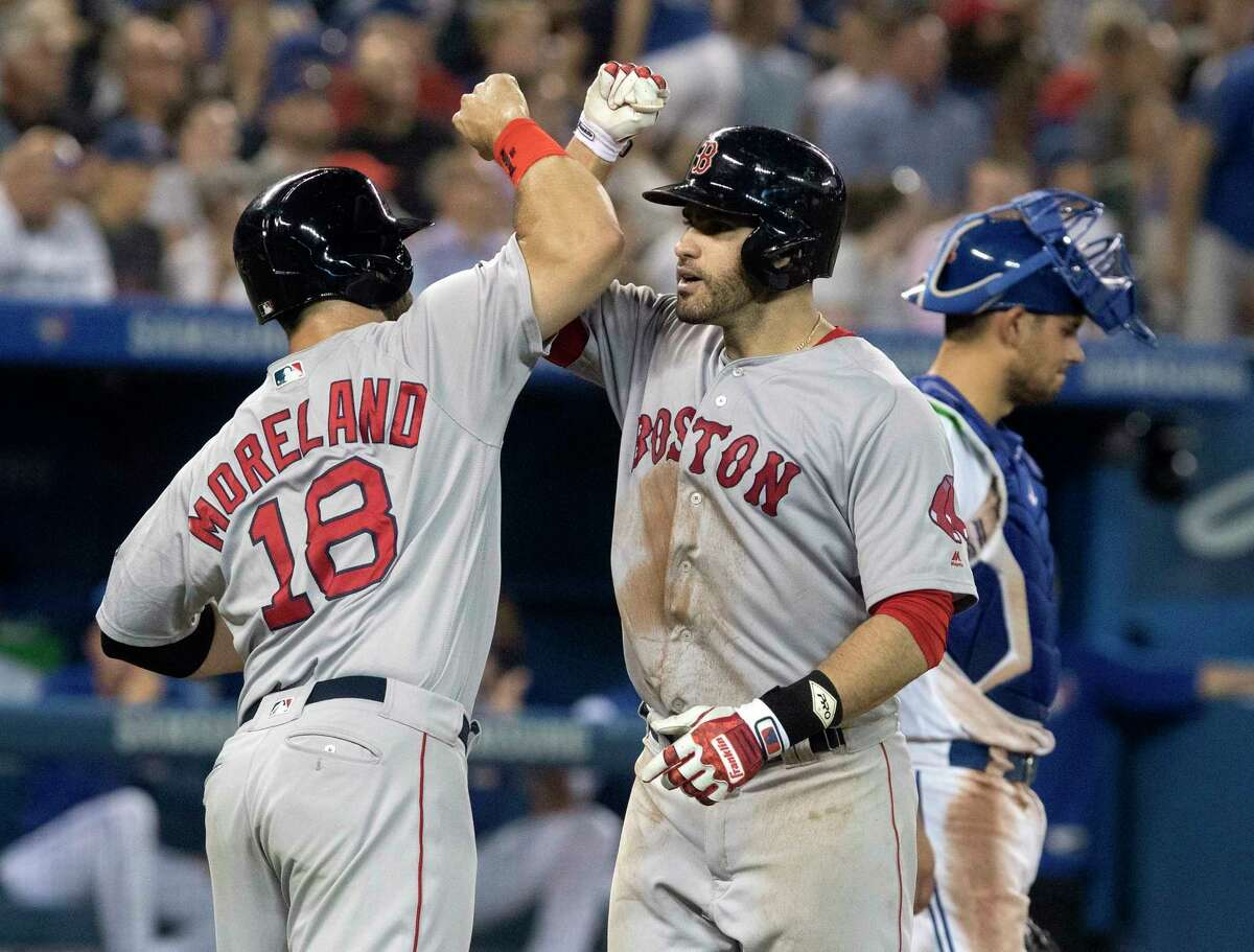 Boston Red Sox' J.D. Martinez is greeted at home plate byMitch Moreland after he hit a three-run home run against the Toronto Blue Jays during the eighth inning of a baseball game Tuesday, Aug. 7, 2018, in Toronto. (Fred Thornhill/The Canadian Press via AP)