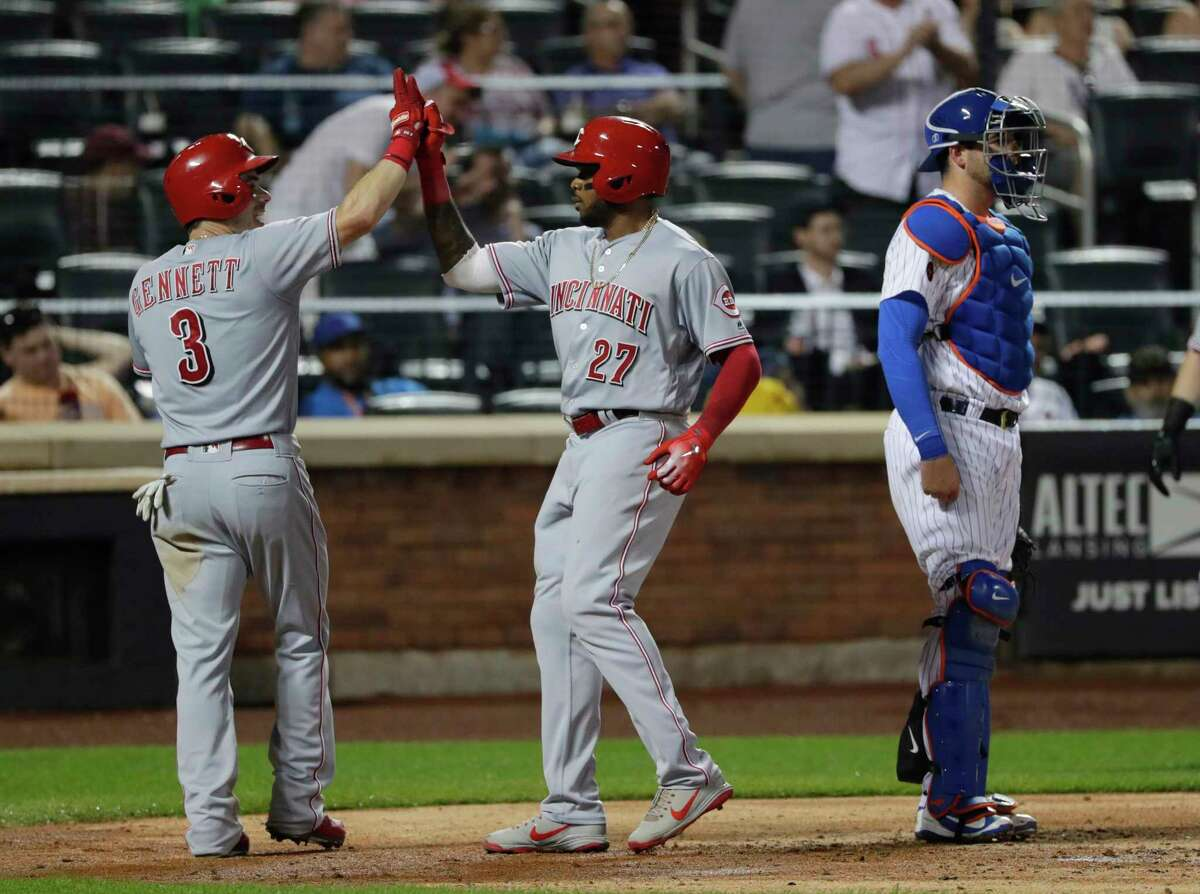 Cincinnati Reds' Phillip Ervin (27) celebrates with teammate Scooter Gennett (3) as New York Mets catcher Kevin Plawecki stands nearby after Ervin hit a two-run home run during the third inning of a baseball game Tuesday, Aug. 7, 2018, in New York. (AP Photo/Frank Franklin II)