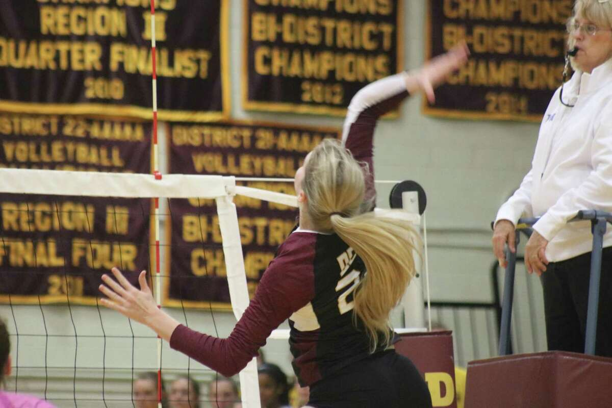 Hope Hawthorne scores a kill in front of referee Dede McPherson during Game 2 action. It gave the team a 21-17 lead.