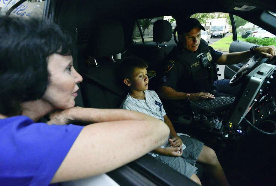 "Stamford Police Sergeant Rick Barbagallo shows seven year-old Dominick Ricucci and his grandmother Rina Ricucci of Stamford the inside of his patrol car during a ""Coffee With a Cop"" event at the Ferguson Library Weed Memorial & Hollander Branch in Stamford, Connecticut on August 7, 2018. This event was part of the National Night Out campaign, hosted by the Springdale Neighborhood Association as part of the annual community-building campaign that promotes police-community partnerships and neighborhood camaraderie to improve safety. Photo: Matthew Brown / Hearst Connecticut Media / Stamford Advocate"
