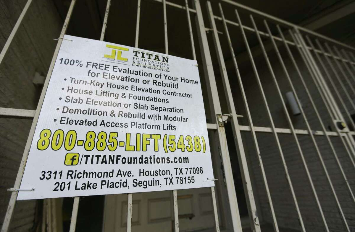 A sign for Titan Foundations & Elevation is attached to the entrance of a home on S. Braeswood Blvd., Wednesday, July 25, 2018 in Houston. Titan Homes was hired by the city to perform the elevations using mostly federal funds, but failed to complete them after running into financial problems. City Council on Wednesday will consider contracts to finish several home elevations abandoned by Titan.