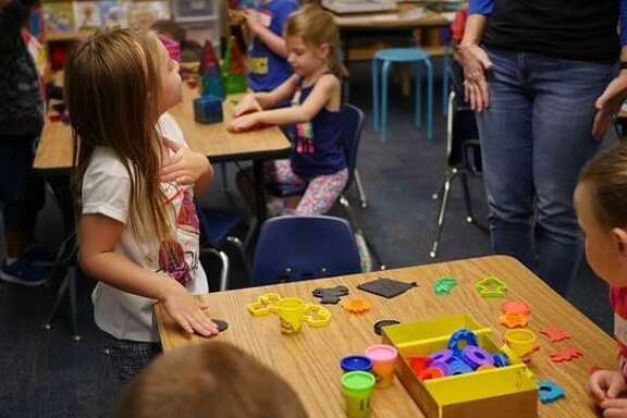 A new kindergartner is excited to show her teacher what she is making with Play-Doh at Westwood Elementary School's Kinder Camp.