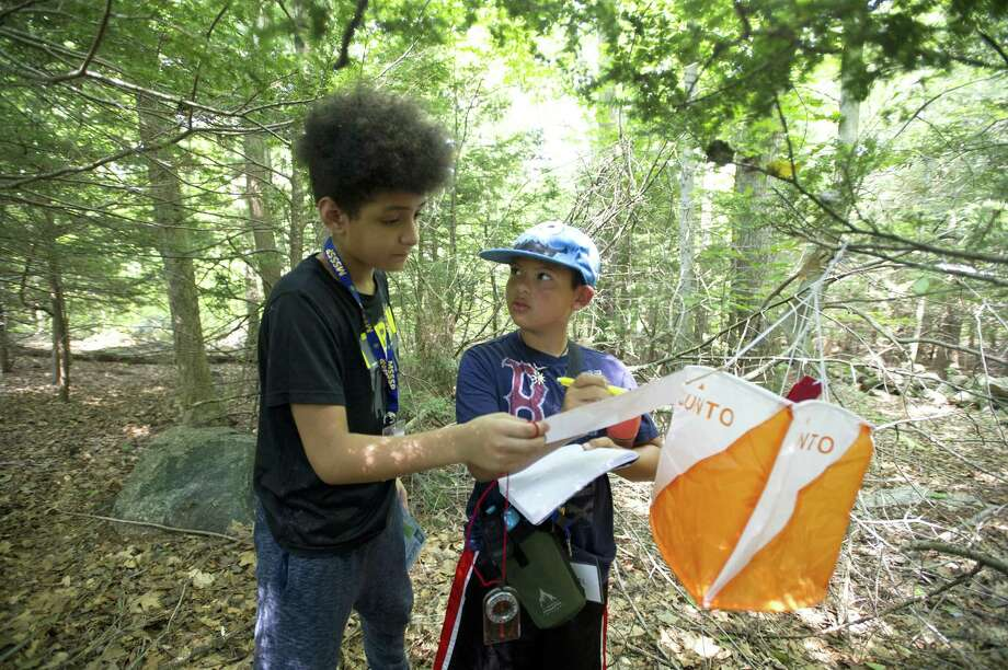 11-year-old Daniel Giron, right, looks at 11-year-old Jonathan Redic while working together to solve a math equation during the Practical Investigations of Science and Math (PRISM) camp at the Bartlett Arboretum in Stamford, Conn. on Tuesday, Aug. 7, 2018. The campers used a compass and various clues to find hidden markers in the woods which contained math problems that needed to be solved. Photo: Michael Cummo / Hearst Connecticut Media / Stamford Advocate
