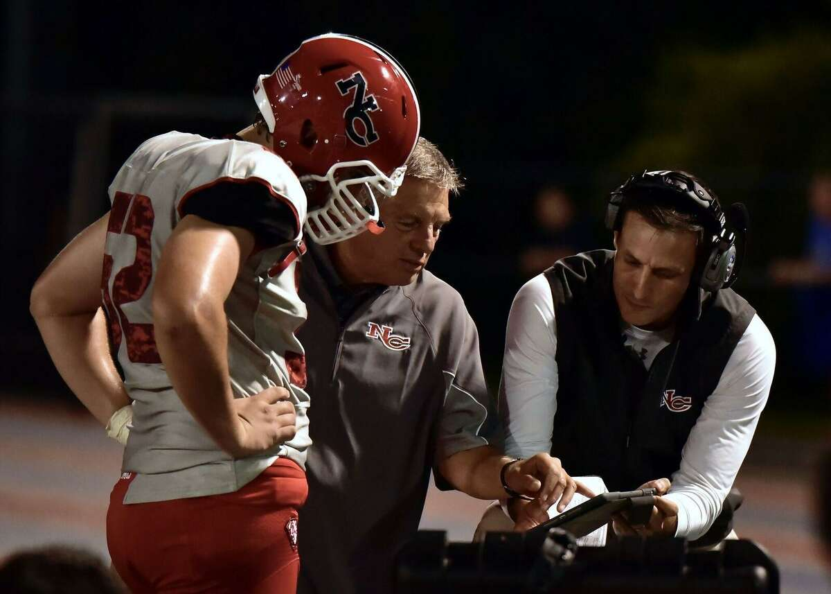 New Canaan defensive coordinator Chris Silvestri, right, goes over adjustments with coach Lou Marinelli and a player.