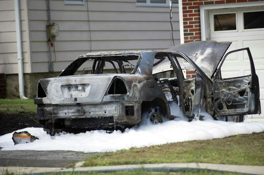 The remains of a charred car sit in the driveway of a Prince Pl. home after it caught fire. Photographed in Stamford, Conn. on Wednesday, Aug. 8, 2018. Photo: Michael Cummo / Hearst Connecticut Media / Stamford Advocate