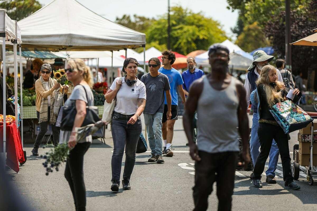 People walk through the farmers market in Berkeley, California, on Tuesday, Aug. 7, 2018.