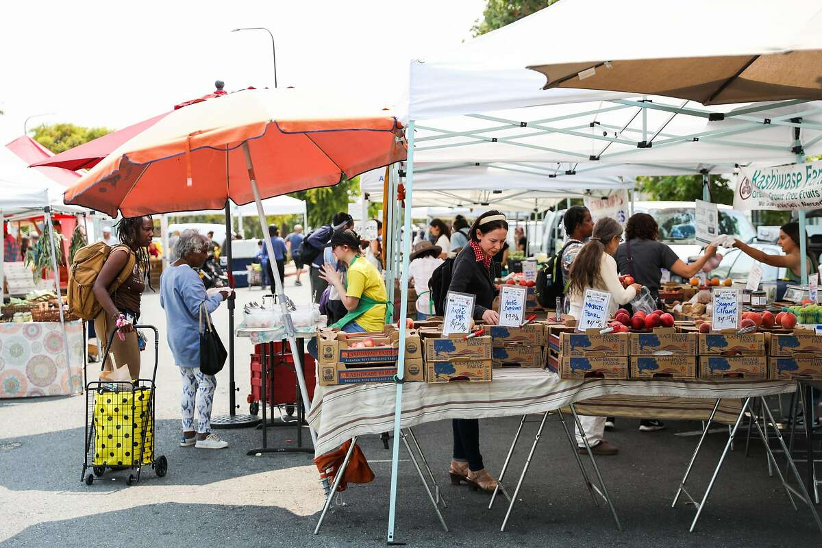 People shop at the farmers market in Berkeley, California, on Tuesday, Aug. 7, 2018.