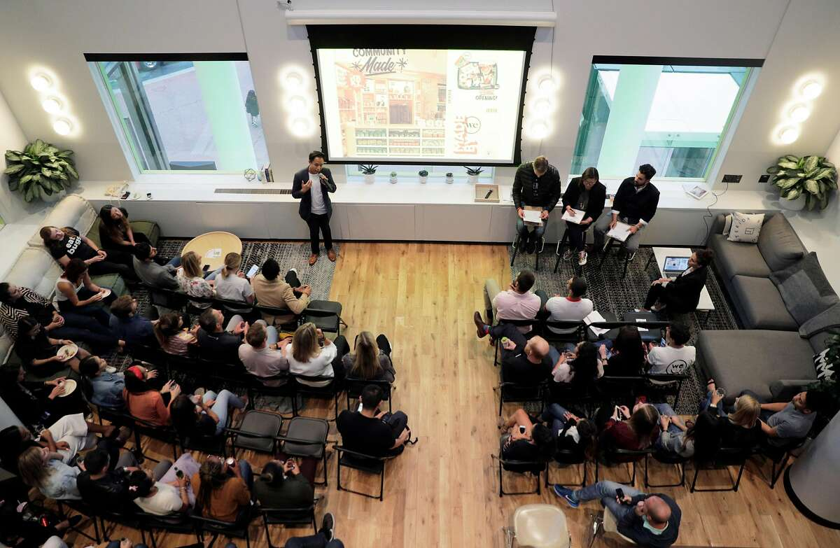 Guests listen as product pitches begin during pitch night for the new WeMRKT concept at WeWork in San Francisco Calif., on Tuesday, August 7, 2018. The company will partner with businesses, both food and dry goods retailers, to hold pop-up shops inside WeWorks, open to members and their guests.