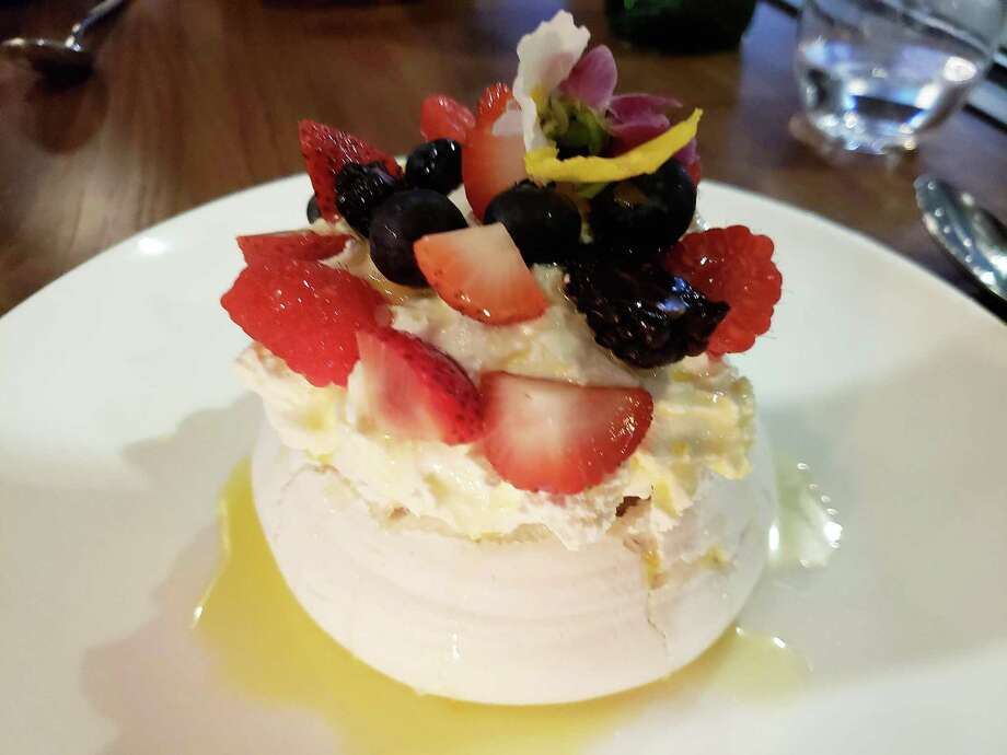 The Pavlova meringue shell, crisp on the outside and fluffy within, was shaped a little like a volcano, the crater filled with vanilla cream and topped with fresh berries at Flinders Lane in Stamford. Photo: Frank Whitman / For Hearst Connecticut Media / Norwalk Hour freelance