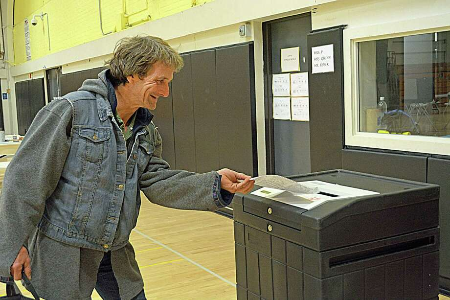 Voters will cast their ballots during Tuesday's primary election. Here, Middletown resident Fred Carroll feeds his into the tabulator at Woodrow Wilson Middle School on Election Day 2017. Photo: File Photo