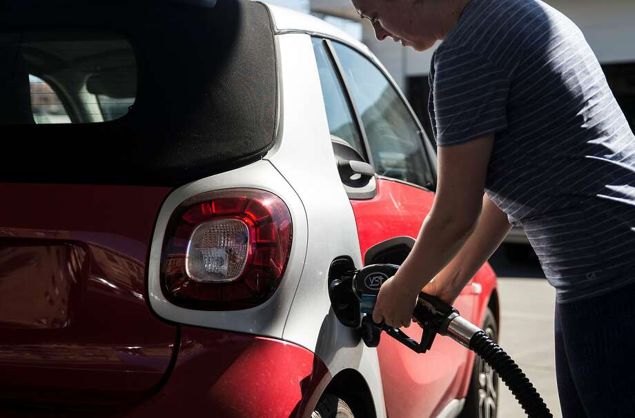 A woman pumps gas into her Smart Car at the Chevron station near 16th and South Van Ness streets in San Francisco, Calif. Saturday, Aug. 4, 2018. Photo: Jessica Christian / The Chronicle