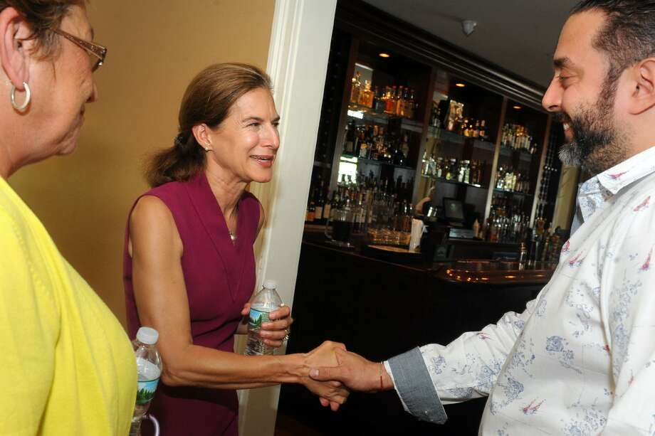 Susan Bysiewicz, democratic candidate for Lt. Governor, shakes hands with owner Frank Basil at Bridge House Restaurant during a tour of the Devon neighborhood of Milford, Conn. Aug. 8, 2018. Photo: Ned Gerard / Hearst Connecticut Media / Connecticut Post