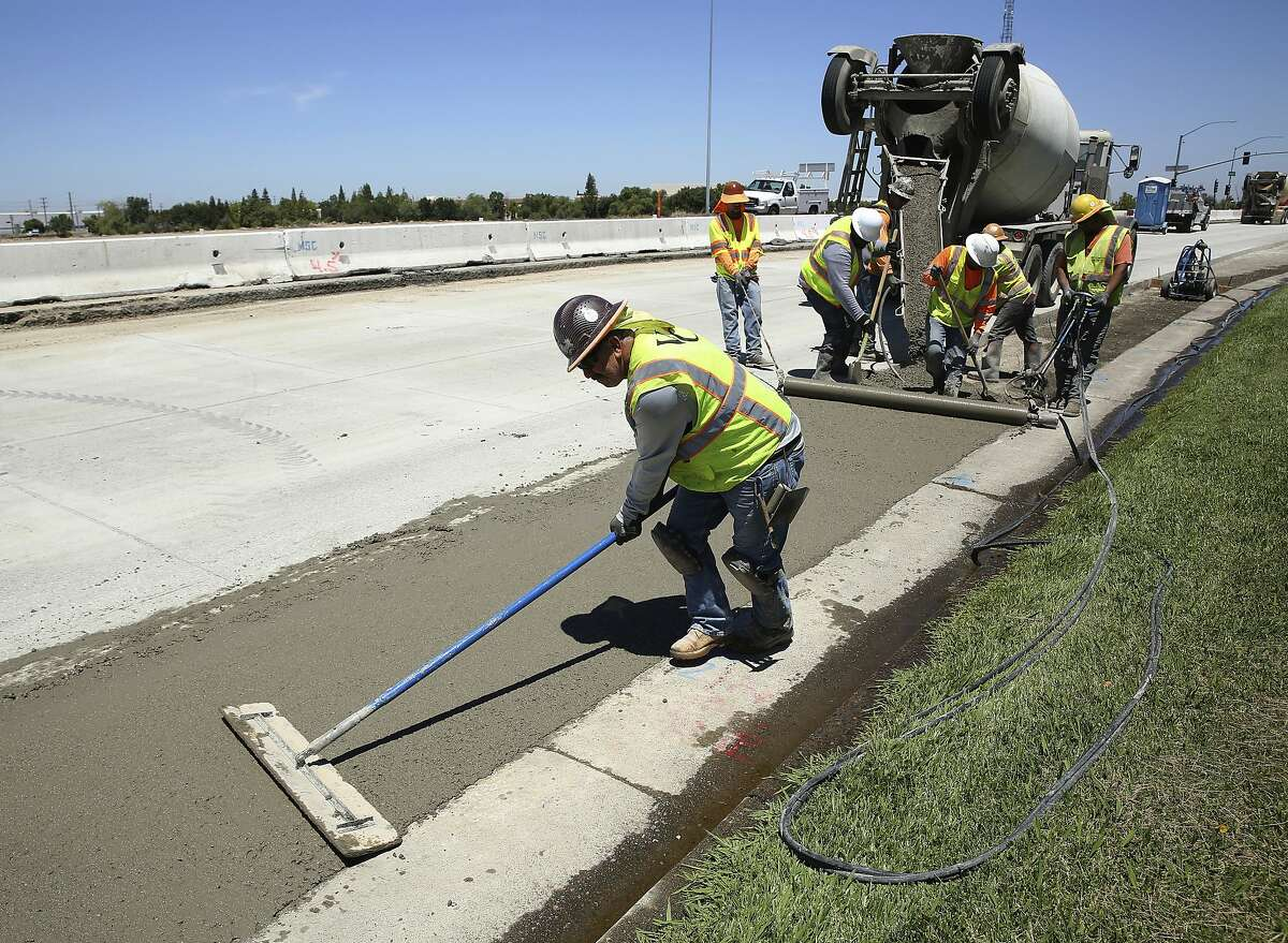 In this July 11, 2018 photo, workers repave a street in Roseville, Calif., partially funded by a gas tax hike passed by the Legislature in 2017. Republican officeholders have plowed money into a November ballot initiative campaign to repeal the tax increase. (AP Photo/Rich Pedroncelli)
