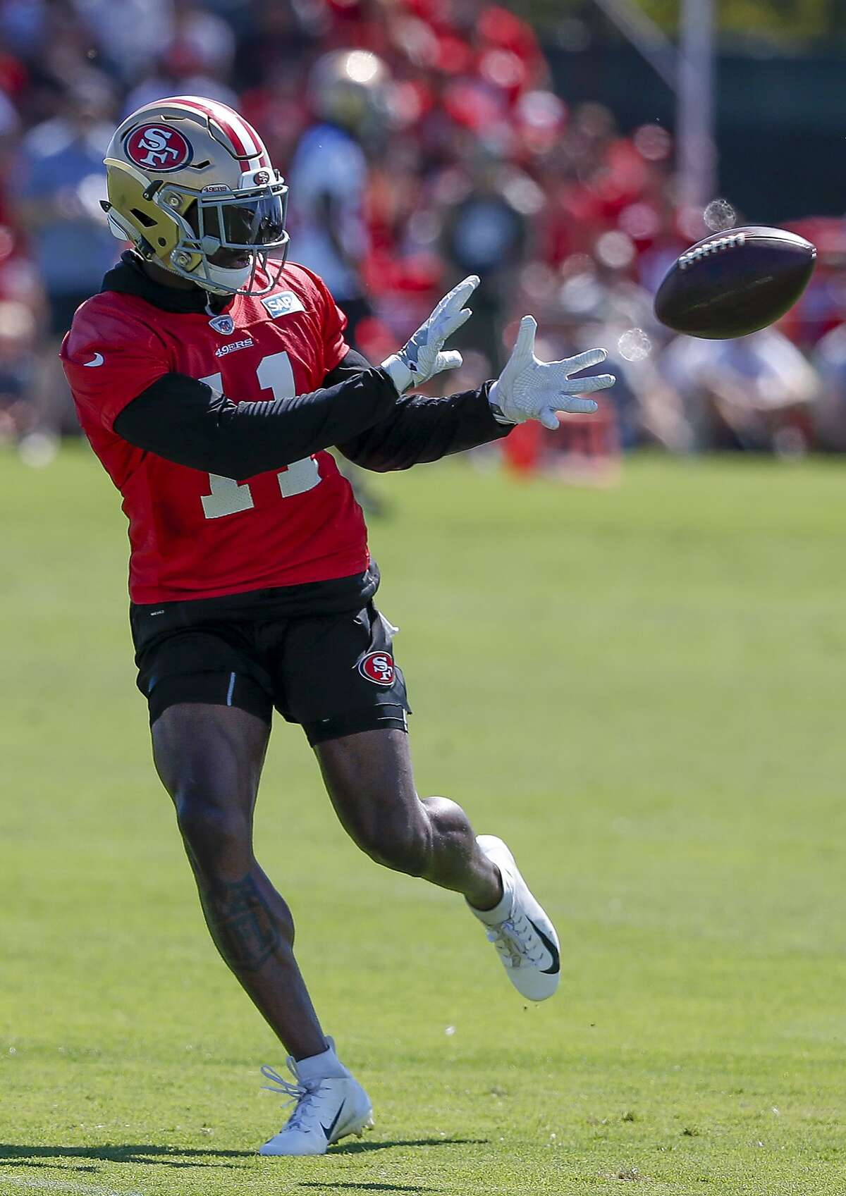 San Francisco 49ers wide receiver Marquise Goodwin (11) catches a pass during NFL football practice at the team's headquarters Friday, July 27, 2018, in Santa Clara, Calif. (AP Photo/Tony Avelar)