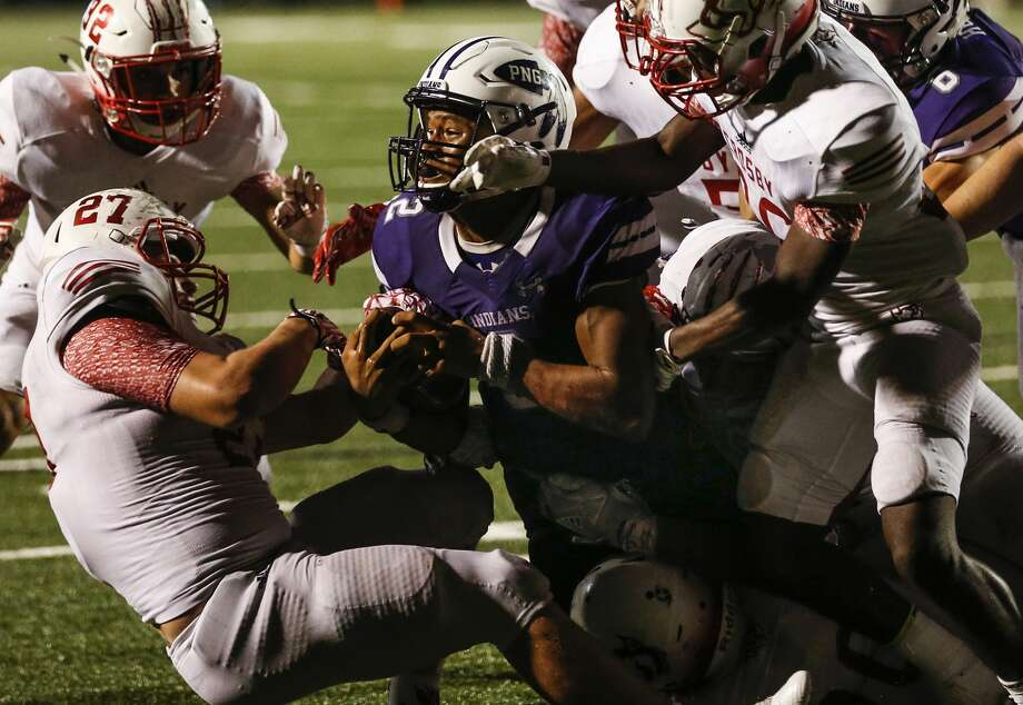 Port Neches-Groves quarterback Roschon Johnson dives into the end zone over Crosby linebacker Hunter Bailey (27) for a 2-yard touchdown, and game winning run, during the fourth quarter of a Class 5A bi-district playoff football game at Stallworth Stadium on Friday, Nov. 17, 2017, in Baytown. Port Neches-Groves advanced in the playoffs with a 72-69 win. ( Brett Coomer / Houston Chronicle ) Photo: Brett Coomer/Houston Chronicle