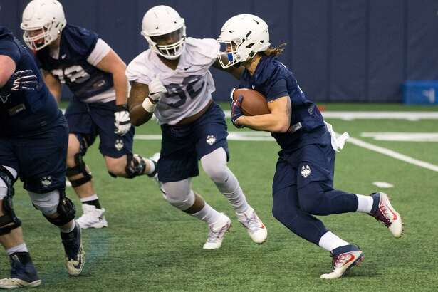 UConn defensive lineman Colton Steer (92) chases a running back during a recent practice in Storrs.