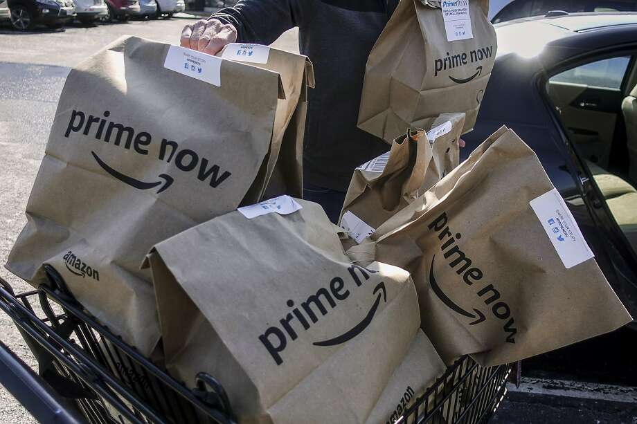 FILE- In this Feb. 8, 2018, file photo, Amazon Prime Now bags full of groceries are loaded for delivery by a part-time worker outside a Whole Foods store in Cincinnati. Amazon, known for bringing items to shoppers' homes, is adding a curbside pickup option at Whole Foods for Prime members. The Whole Foods move announced Wednesday, Aug. 8, 2018, is the latest by Seattle-based Amazon.com Inc. since it took control of the grocery chain a year ago. (AP Photo/John Minchillo) Photo: John Minchillo, Associated Press