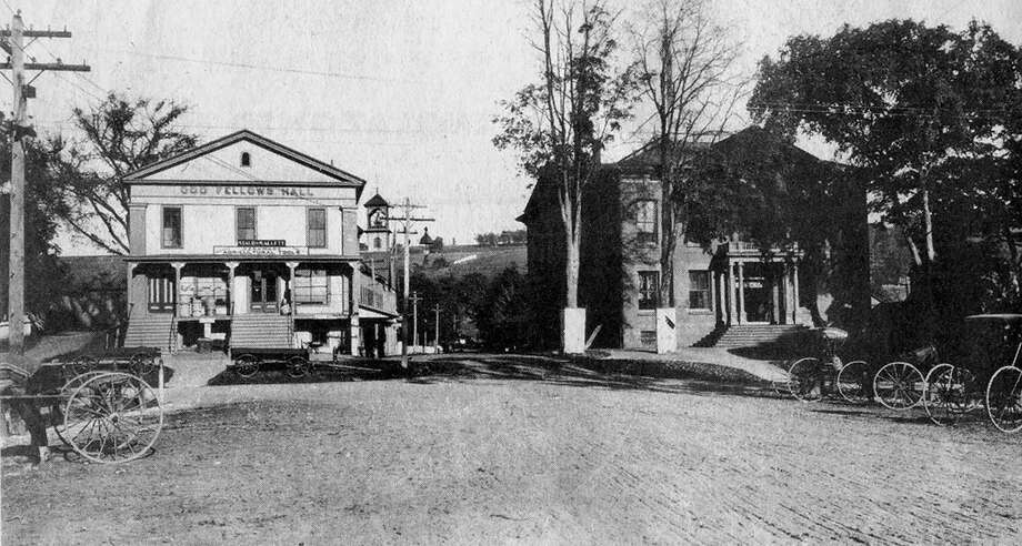 """This late 19th-century photographic view from the west side of Main Street in New Milford's historic village shows parking for horses and carriages along the plaza between Church and Bank streets was arranged much the same as today for motorized vehicles. Note the building to the left now called home by the Village Center for the Arts was then called the Odd Fellows Hall. It had originally been built for use as a church but soon became the home for more than a century for the Village Hardware business. New Milford's town hall, the Roger Sherman Town Hall, was shaded by towering elm trees such as those that lined the Village Green for many years. Until its entrance was altered several decades ago, the town hall as it appears here matches that of its sister town hall in Great Barrington, Mass. If you have a """"Way Back When"""" photograph to share, contact Deborah Rose at drose@newstimes.com or 860-355-7324. Photo: Contributed Photo / Contributed Photo / The News-Times Contributed"""