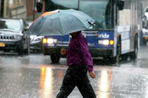 A pedestrian crosses State Street under an umbrella as yet another rain storm hits the region Wednesday August 8, 2018 in Albany, NY.  (John Carl D'Annibale/Times Union)