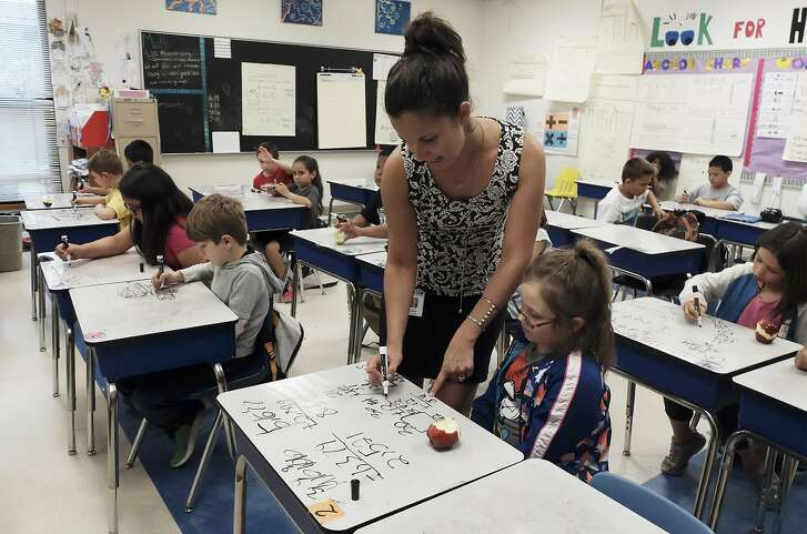 Second-grade Math Teacher Savanna Bartolo helps Caydence Huffman with a math problem in class on Thursday, May 10, 2018. Houston-based nonprofit Children at Risk's 2018 school rankings, which highlight high-performing high-poverty schools, show that San Antonio is not closing the gap with the other big cities in Texas and SAISD in particular is not moving the needle fast enough. This year's featured school is McQueeney Elementary in Seguin ISD. (Kin Man Hui/San Antonio Express-News)