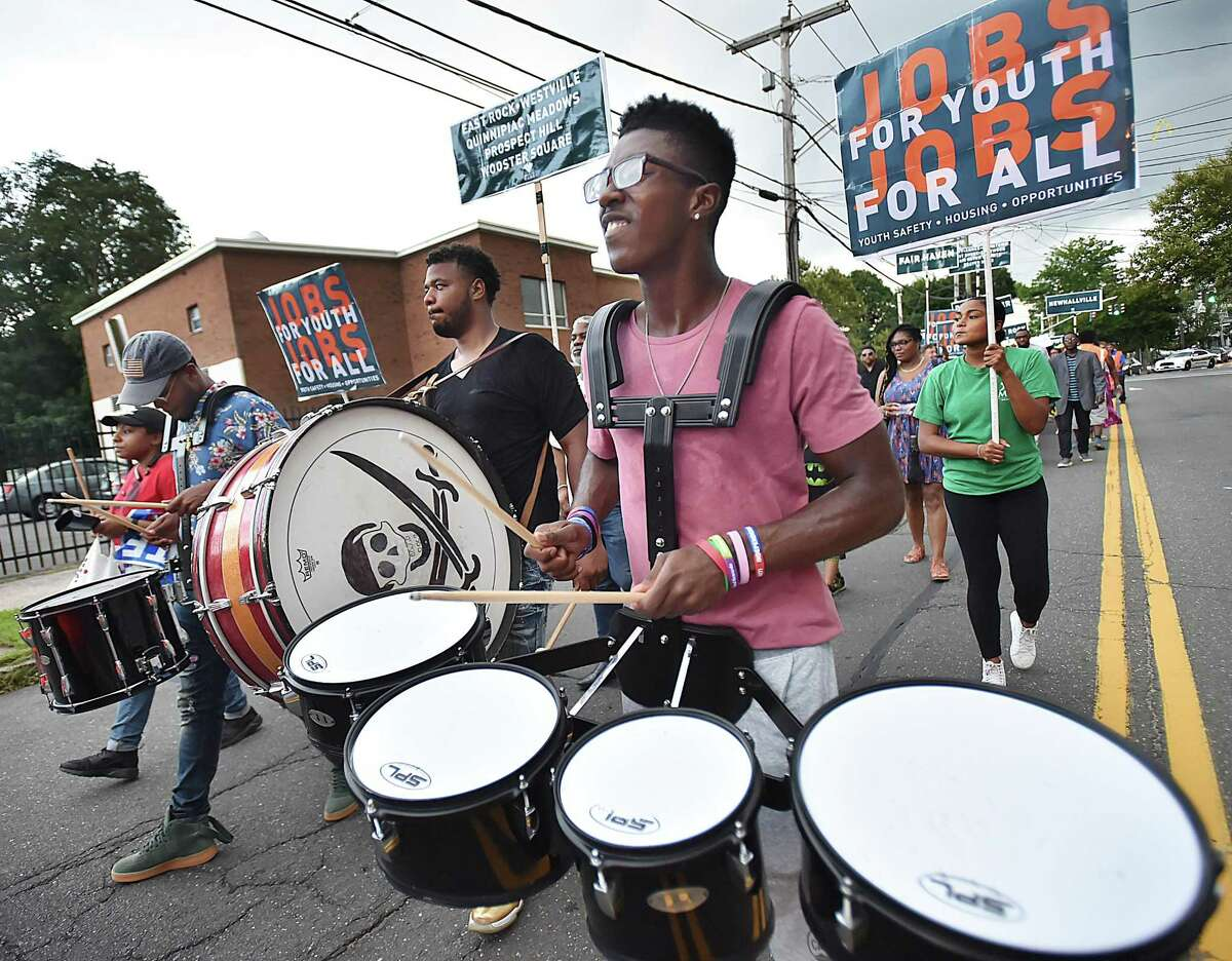 New Haven residents Jayshon Edwards, Charlie Wilson and Ron Hurt Jr., right to left, lead the march through the Dixwell neighborhood Wednesday, August 8, 2018, focused on youth safety, good jobs, affordable housing. The rally starting at the Goffe Street Park and ending at the Ella B. Scantlebury Park was organized by New Haven Rising and the anti-violence group, Ice the Beef.