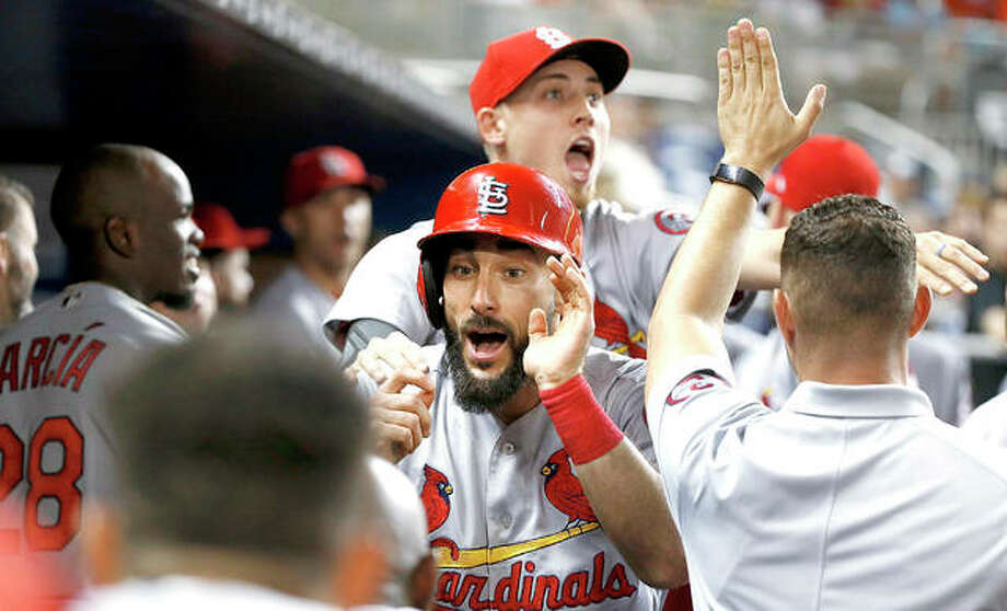 The Cardinals' Matt Carpenter, center, celebrates with teammates after hitting a home run in the sixth inning of Wednesday night's game in Miami against the Marlins. Photo:     AP
