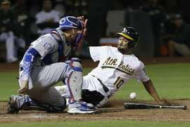 Oakland Athletics' Marcus Semien, right, scores against Los Angeles Dodgers catcher Yasmani Grandal during the eighth inning of a baseball game in Oakland, Calif., Wednesday, Aug. 8, 2018. (AP Photo/Jeff Chiu)