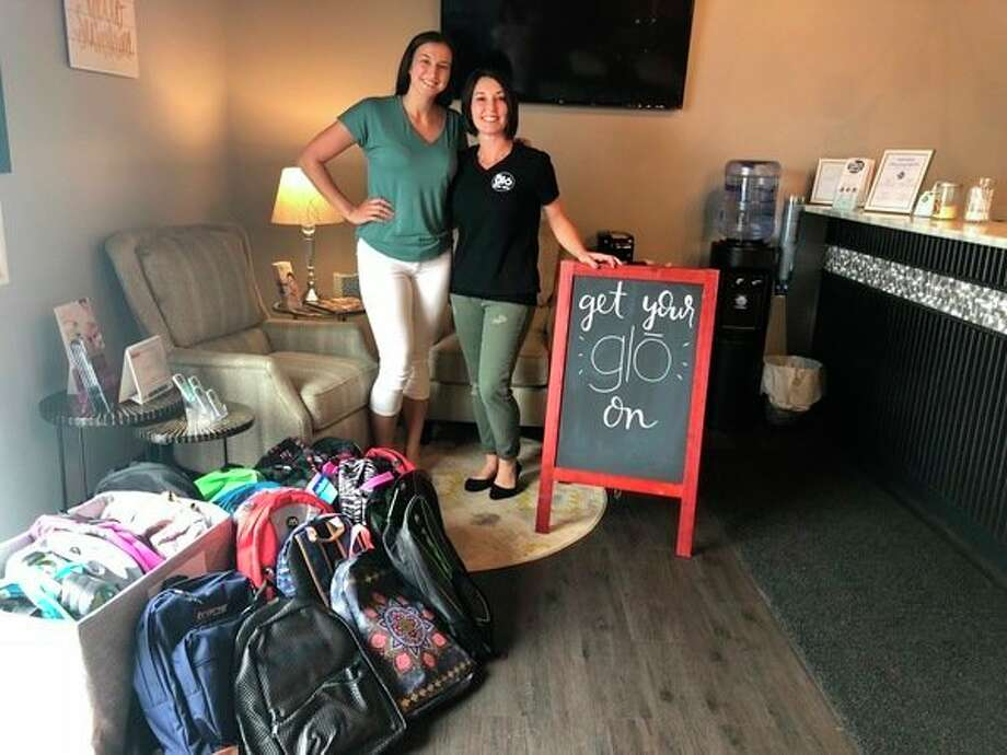 Salena Dodman and Jillian Brady from Glo Skin Salon stand with donations from Glo Skin Spa employees and customers. The backpacks filled with school supplies will be given to junior high and high school foster youth through the Midland/Gladwin Department of Health and Human Services. (Photo provided)