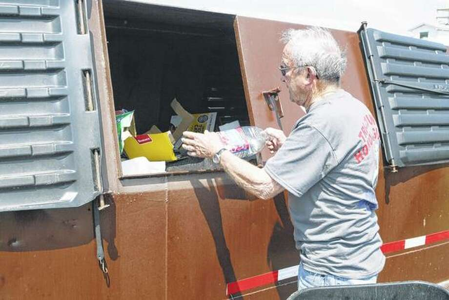 Carl Edwards of White Hall places items in a new recycling container at North Greene Junior and Senior High School. Photo:       Greg Olson | Journal-Courier