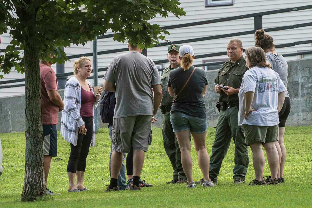 EnCon officers brief family members and their friends near the side of the Mohawk River near Lock 2 and wait for word of a missing 14 year old male on the Thursday Aug. 9, 2018 in Waterford, N.Y.(Skip Dickstein