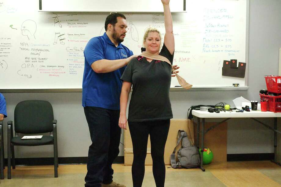 Public school teacher Carol Waters volunteers as first aid instructor Spencer Frink demonstrates the technique for treating a bleeding wound in the neck or shoulder. Photo: Kirk Sides / Houston Chronicle / © 2018 Kirk Sides / Houston Chronicle