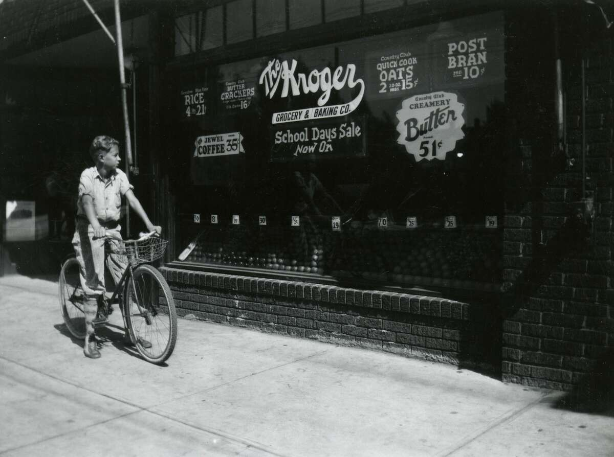 A boy on a bicycle stops to look at the window of Kroger's grocery store which advertises a back to school sale, College Hill, Ohio, 1928.