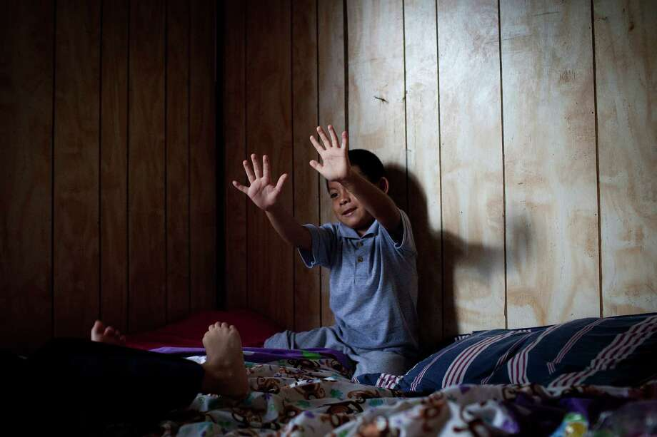 Adonias plays with his cousin in their cramped house. Photo: Photo For The Washington Post By Charlotte Kesl. / Charlotte Kesl for The Washington Post.