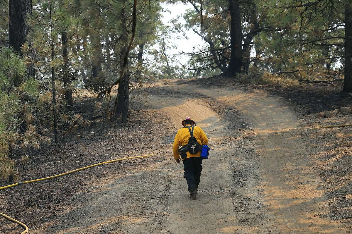 A firefighter hikes up a trail in an area burned by the Ranch fire around Clearlake, Calif., Aug. 8, 2018. The Mendocino Complex fire system, a combination of the Ranch fire and the River fire, has grown to more than 300,000 acres. Billowing smoke from the historic wildfire season has caused hazardous air conditions across the state, prompting air quality alerts and forcing many residents to take refuge indoors to avoid unhealthy exposure to bad air. (Jim Wilson/The New York Times)