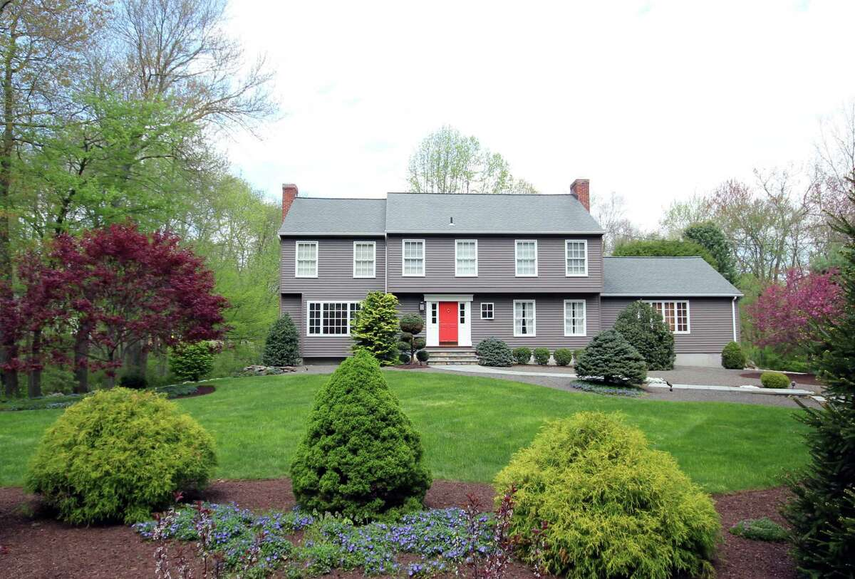 The taupe-colored colonial house at 24 Old Easton Turnpike sits on a two-acre level property that adjoins a 8.5-acre protected open space, managed by the Aspetuck Land Trust.