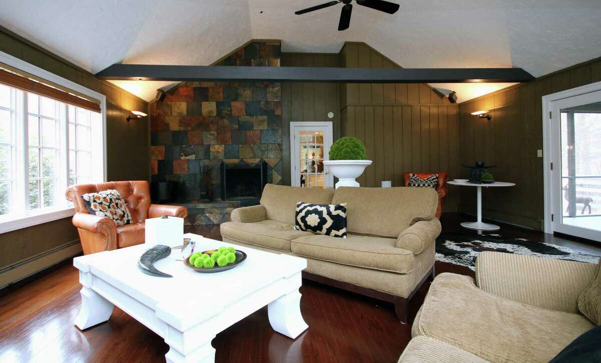 The family room has a vaulted ceiling and beams and French doors to the screened porch.