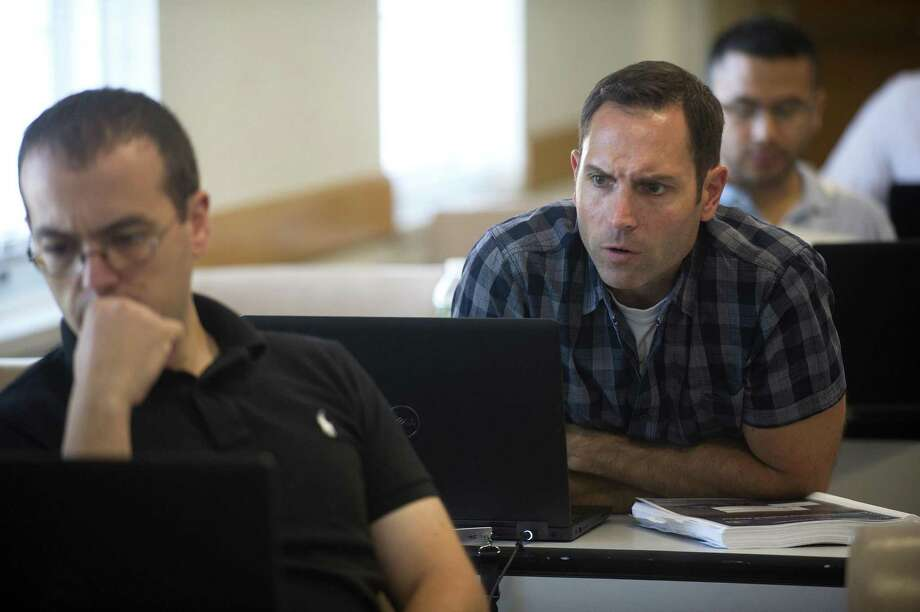 Westport police detective Marc Heinmiller looks over the shoulder of Wilton police officer Steve Rangel while learning the Cellebrite program, which extracts evidence and data from cellphones, during a class inside the Westport Police Station on Jessup Rd. in Westport, Conn. on Wednesday, Aug. 8, 2018. Photo: Michael Cummo / Hearst Connecticut Media / Stamford Advocate