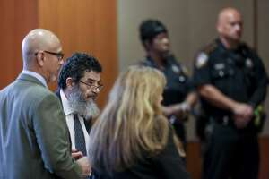 """Ali Mahwood-Awad Irsan, second from left, stands in the courtroom before the start of testimony from witnesses in Jordan in his capital murder trial at the Harris County Civil Courthouse Thursday Aug. 9, 2018 in Houston. Irsan is accused of orchestrated two separate but related """"honor killings"""" in 2012."""