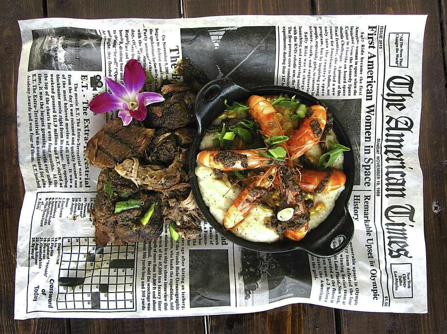 Jerk pork, left, and shrimp and grits served on a wax-paper replica of a newspaper page from The Jerk Shack. Photo: Mike Sutter /Staff