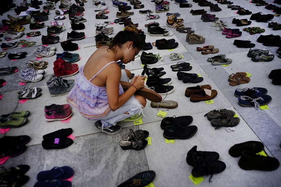 A woman places one of the hundreds of shoes in memory of those killed by Hurricane Maria in front of the Puerto Rico Capitol, in San Juan, Friday, June 1, 2018.  Puerto Rico's Institute of Statistics announced that it has sued the U.S. territory's health department and demographic registry seeking to obtain data on the number of deaths following Hurricane Maria as a growing number of critics accuse the government of lacking transparency. (AP Photo/Ramon Espinosa) Photo: Ramon Espinosa, AP