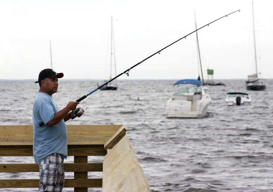 Resident Gerardo Montes enjoys fishing at Seaside Park in Bridgeport, Conn., on Friday, Aug. 3, 2018. Photo: Christian Abraham / Hearst Connecticut Media / Connecticut Post